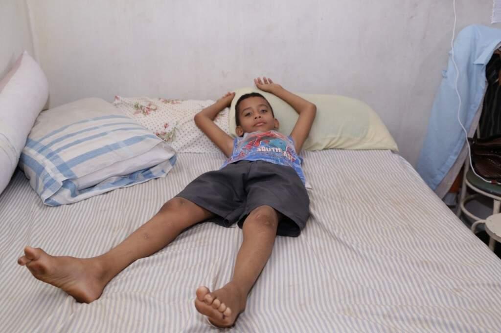 Na edícula de dois quartos e um banheiro cedida pela vizinha, João mostra o quarto em que divide a cama com os pais (Foto: Kísie Ainoã)