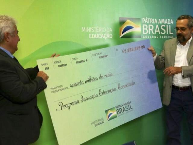O ministros de ciência, tecnologia e Inovação, Marcos Pontes e da Educação, Abraham Weintraub, segurando o cheque simbólico dos valores. (Foto: Fabio Rodrigues Pozzebom/AgênciaBrasil)