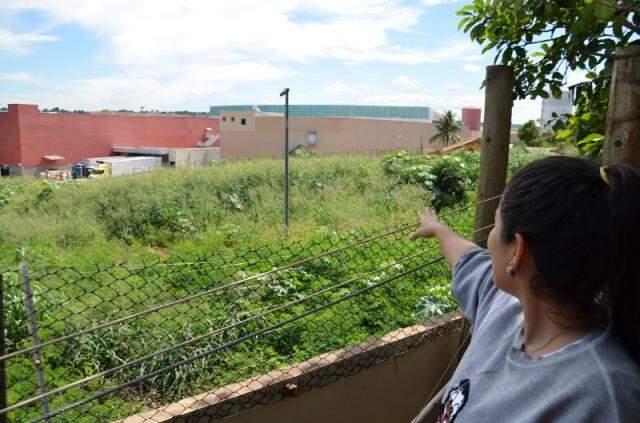 Juliana mostra o terreno vizinho. (Foto: Vanderlei Aparecido)