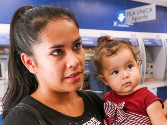Maria Aparecida Borges, com sua filha de oito meses, foi sacar o FGTS (Foto: Henrique Kawaminami)