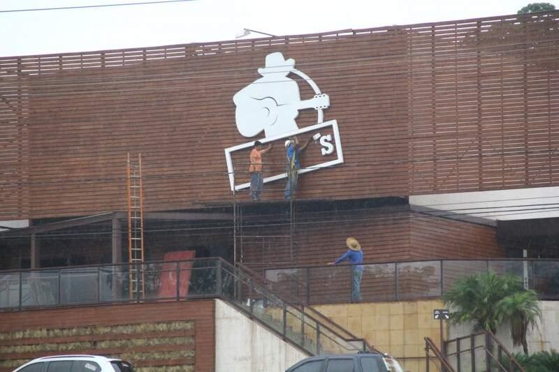 Funcionários retiram a logo do prédio localizado na Afonso Pena (Marcos Ermínio)