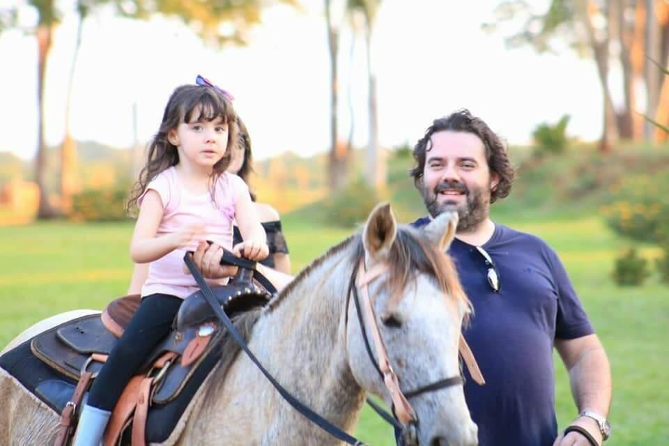 O pai ensinado a filha montar em cavalo (Foto: Estância Itália)