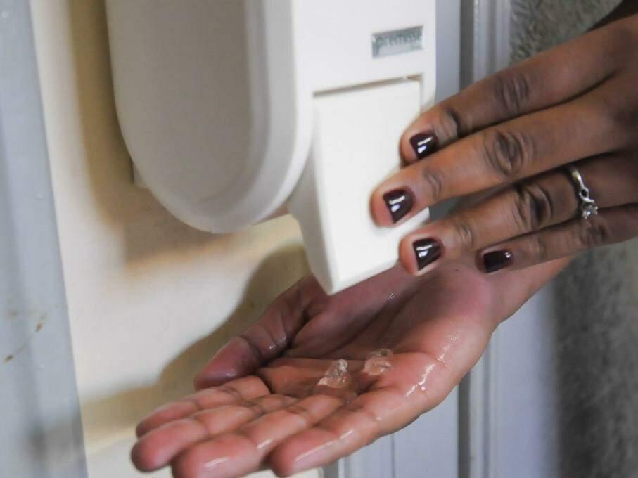 Mulher passa álcool em gel nas mãos; produto é alternativa para quando não há como lavá-las com água e sabão (Foto: Paulo Francis)