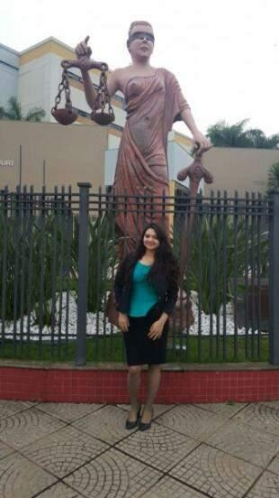 Feliz da vida, em frente ao símbolo do Direito.