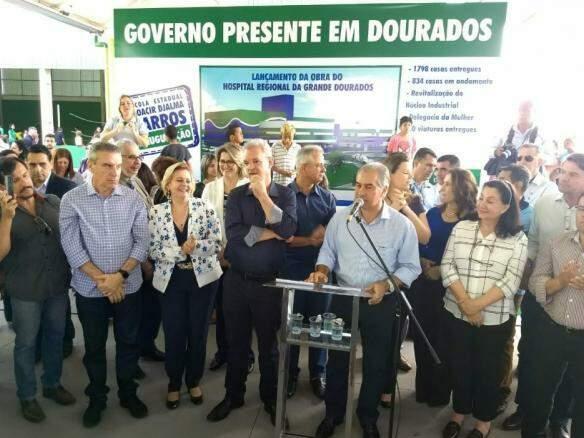 Governador Reinaldo Azambuja, no centro, em discurso durante agenda em Dourados. (Foto: Helio de Freitas).