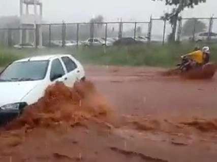 Chuva forte provoca alagamento e deixa carro no meio da rua
