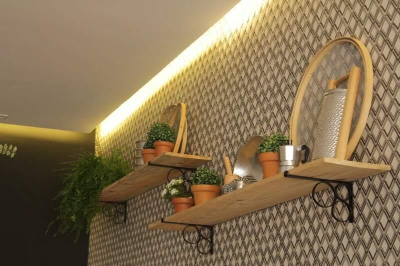 Na parede revestida com cerâmica, vasos de barros e utensílios de cozinha compõe a decoração.