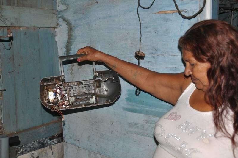 """Maria mostra o rádio velho que separa para os """"carrinheiros"""" que passam pelo bairro. (Foto: Marcelo Calazans)"""