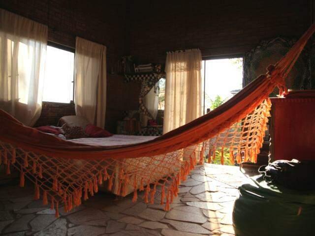 O quarto de Hérica, com a rede na entrada, piso de pedra e decoração rústica com mandalas. (Foto: João Paulo Gonçalves)