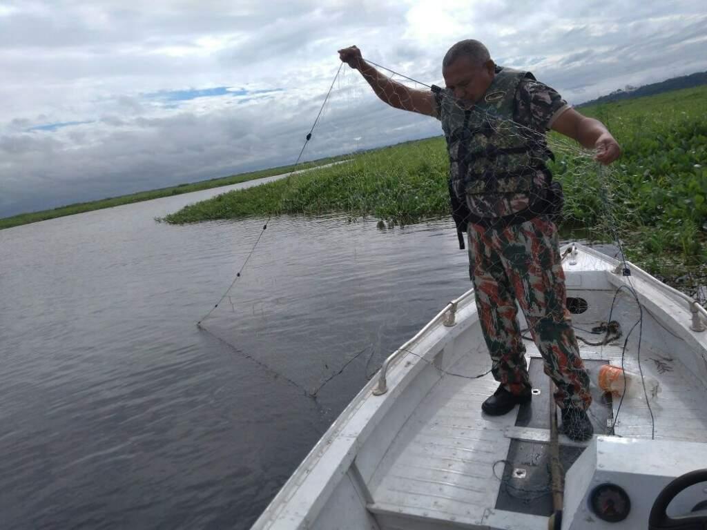 Policial ambiental durante apreensão de rede de pesca (Foto: Divulgação/ PMA)