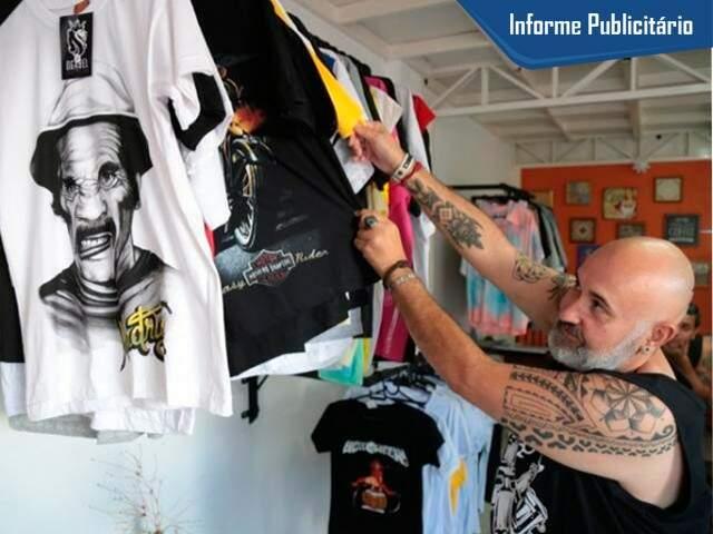 João mostra arara cheia de camisetas. (Foto: Fernando Antunes)