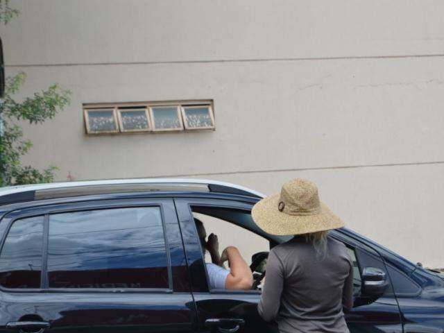 Os motoristas abaixam o vidro do carro para que Aline possa vender as cocadas (Foto: Alana Portela)