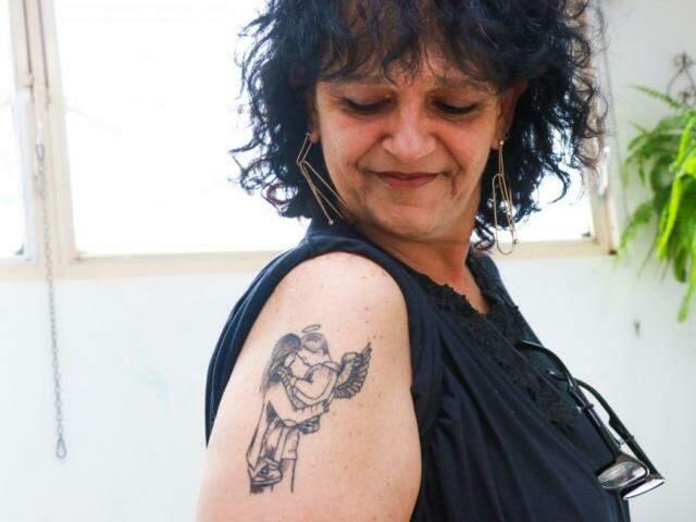 Tatuagem representa João no colo de Meyre. (Foto: Henrique Kawaminami)