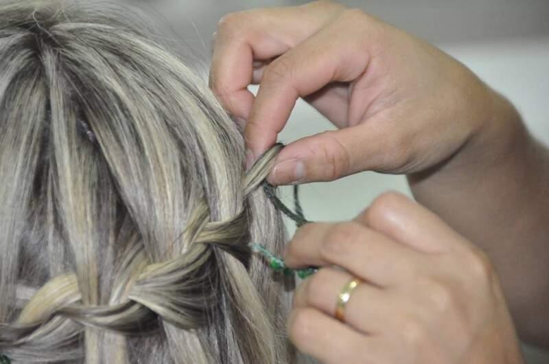 Depois de trançar as mechas, passe o cordão de lantejoulas por baixo e no meio da trança.