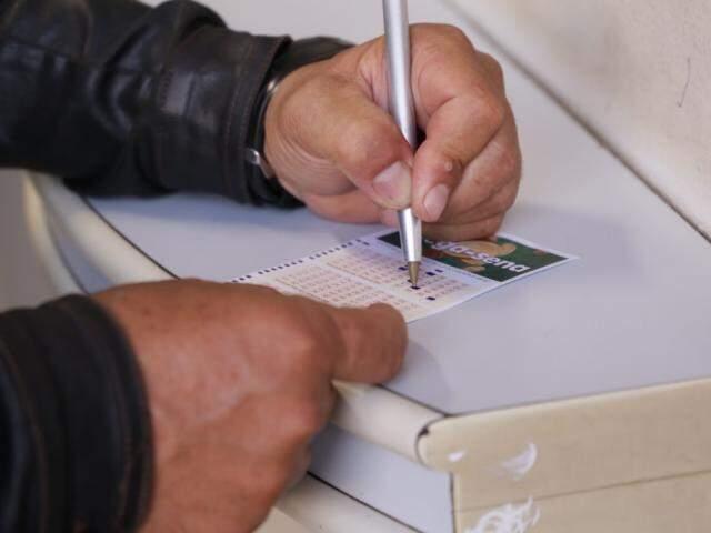 Homem marca números em jogo da Mega-Sena (Foto: Arquivo)