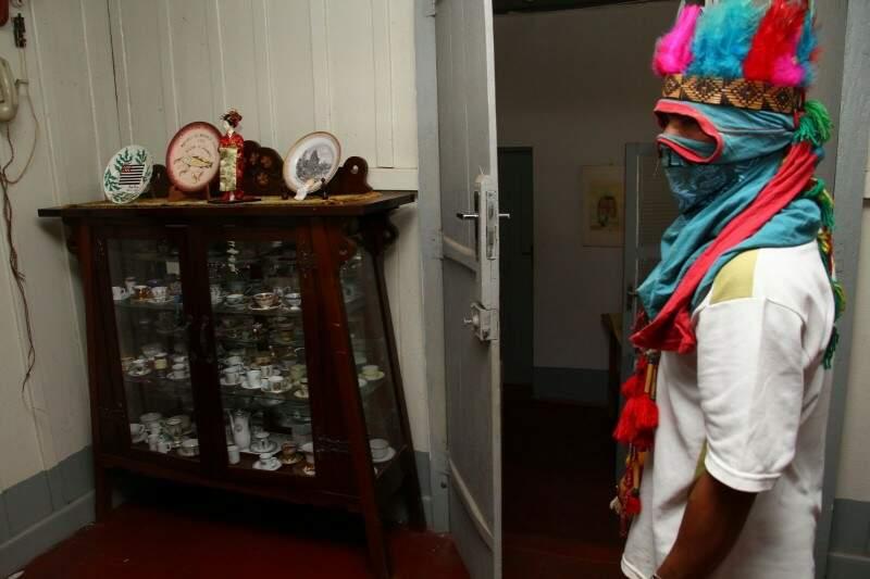 Índio observa as louças de porcelana em um móvel na casa central da sede da Primavera (Foto: Marcos Ermínio)