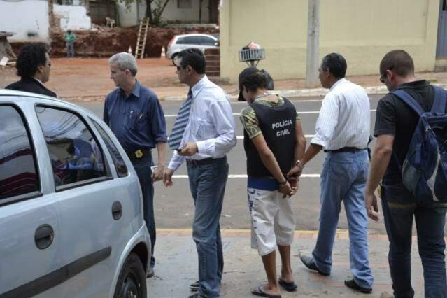 Adolescente e policiais, na saída da 1ª Delegacia de Polícia. (Foto: Simão Nogueira)