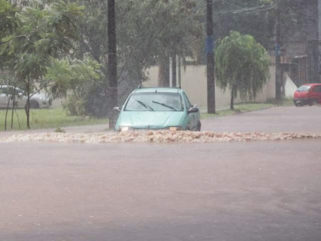 Motorista se arrisca ao atravessar rua do entorno da Lagoa Itatiaia completamente alagada (Foto: Marcos Maluf)