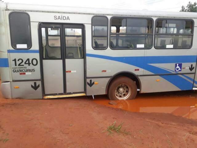 Ônibus ficou preso pela traseira no chão ao passar pelo buraco com água na rua (Foto: Direto das Ruas)