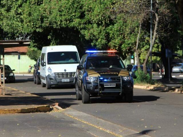 Van branca com presos é escoltada por duas viaturas da PF, na entrada da sede, em Campo Grande. (Foto: Marina Pacheco).