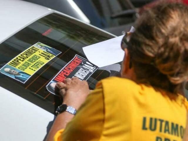 Integrante de movimento adesivando carros na Avenida Afonso Pena (Foto: Marcos Maluf)