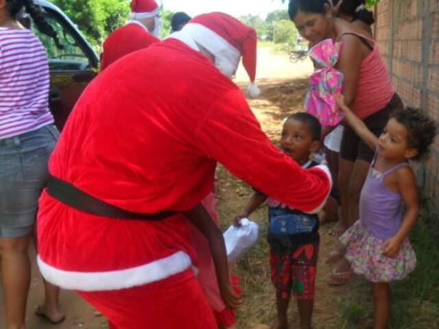 Voluntário entrega brinquedos para menino e menina.