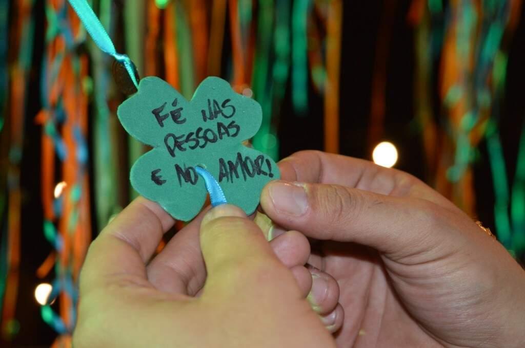 """Recado com a frase """"Fé nas pessoas e no amor"""" sendo amarrado (Foto: Alana Portela)"""