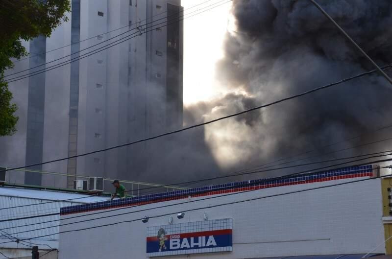 Homem estava sobre o telhado da loja e bombeiros suspeitam dele (Foto: Vanderlei Aparecido)