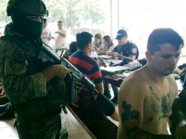 Policial paraguaio vigia presos quinta-feira; à direita está Evandro Padilha, que seria membro do PCC (Foto: ABC Color)