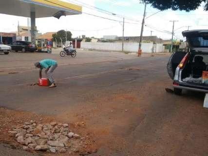Morador do bairro Pedrossian faz 'tapa buraco' em ruas esburacadas