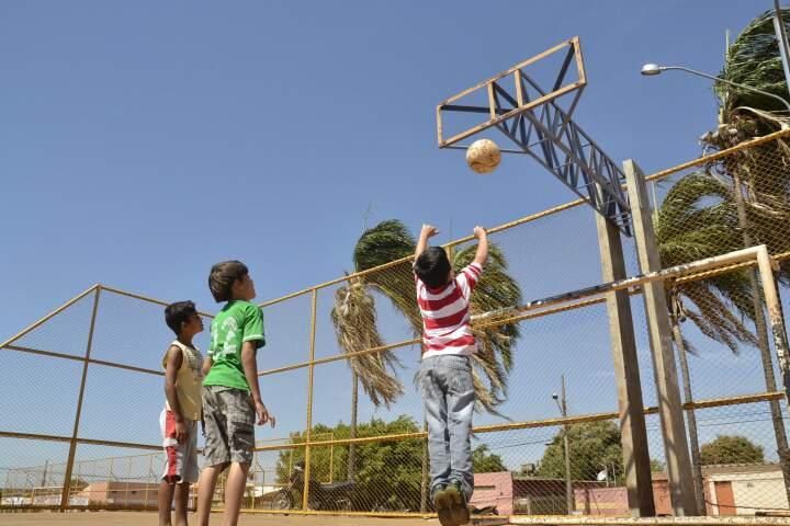Crianças brincam mesmo sem a tabela de basquete.