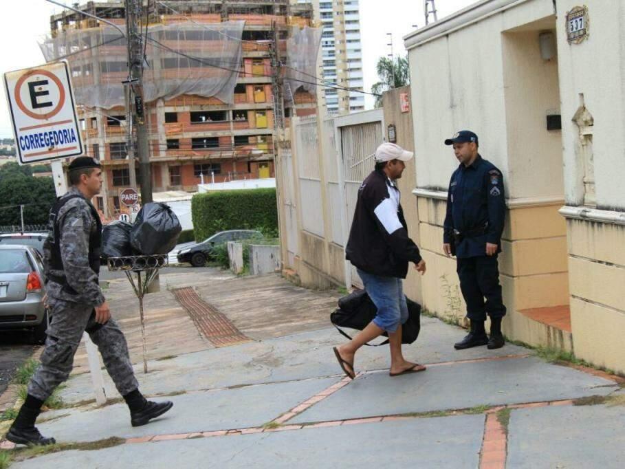 De boné e bermuda, homem, possivelmente um dos PMs alvos da operação, chega à sede da Corregedoria com mala na mão (Foto: Marina Pacheco)
