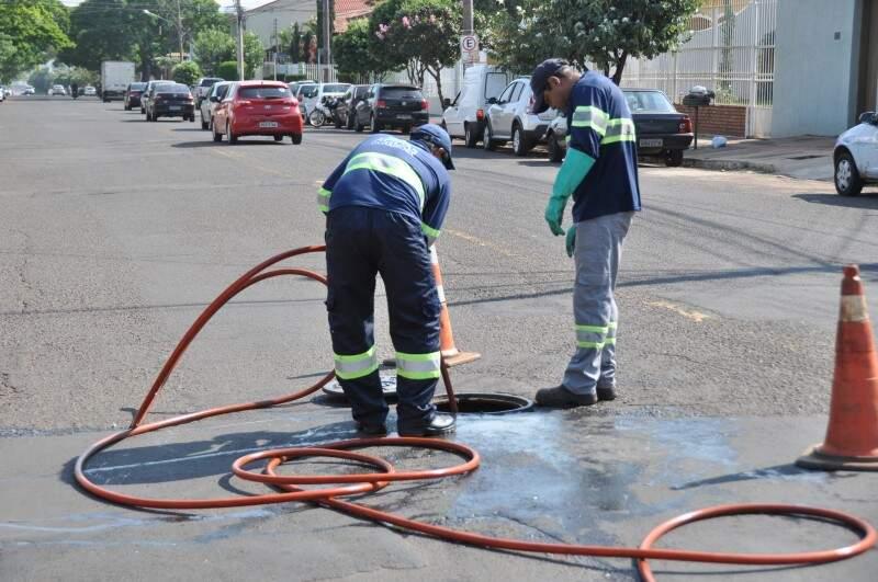 Funcionários limpando os tampões do esgoto que ficam na rua. (Foto: Marcelo Calazans)