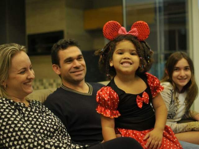 No sofá de casa, preparada para uma foto de família, é que os Machado Campanile Braga contam sua história de adoção. (Foto: Alcides Neto)