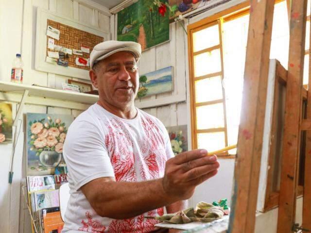 Antônio Lima não abre mão da casinha de madeira que virou combustível para seguir pintando. (Foto: Henrique Kawaminami)