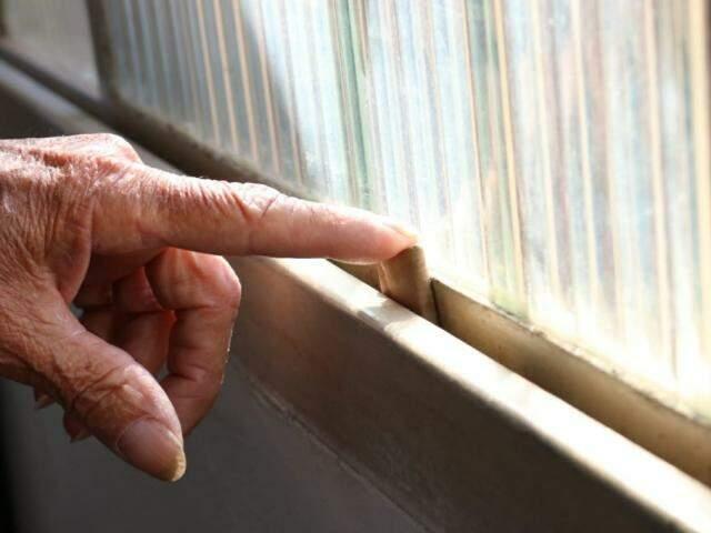 Idoso colocou pedaço de papelão na janela para tentar diminuir o barulho do vidro batendo com a intensidade do som (Foto: Henrique Kawaminami)