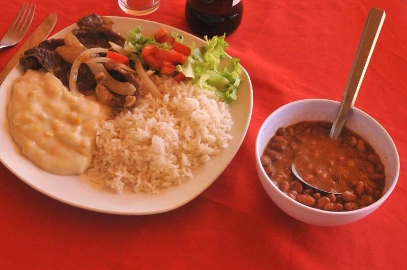 Prato com bife acebolado, creme de milho, arroz, feijão e salada.