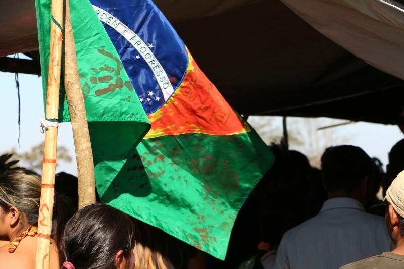 Bandeira do Brasil manchada de tinta vermelha é içada em barraco onde estava o caixão (Foto: Helio de Freitas)
