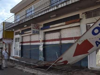 Letreiro de loja cai, impede abertura de portão e bloqueia calçada