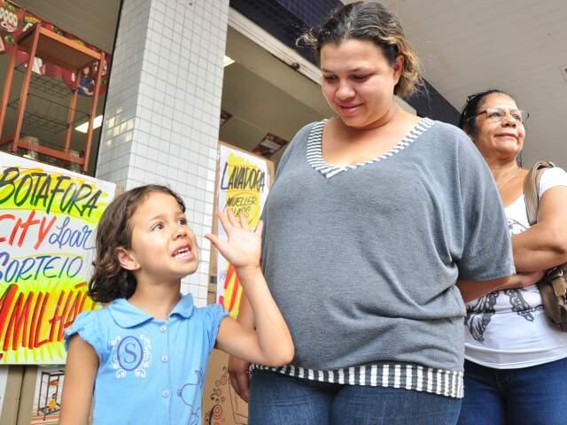 Na fila, menina de cinco anos acompanha a mãe na espera pelas compras.