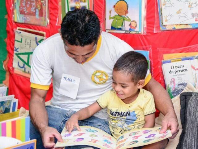 Adulto contando uma história para uma criança. (Foto: Andrezza Mariot/ReproduçãoAgênciaBrasil)