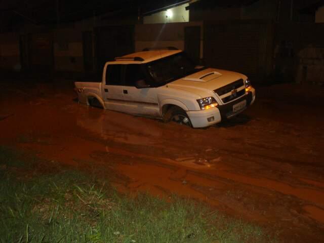 Rodas do veículo somem em meio ao barro em rua, que ficou intransitável após a chuva. (Foto: Sebastião Macedo)