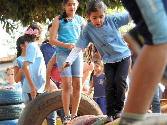 Crianças de escola municipal brincam com pneus adaptados para a diversão. (Foto: Divulgação/PMCG)