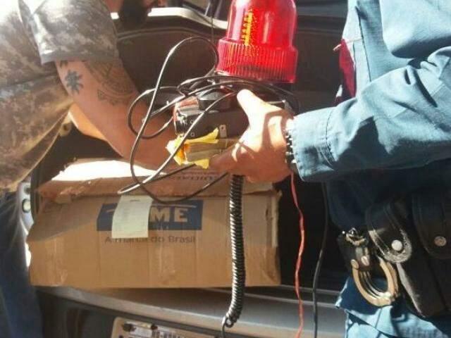Ajudado por irmão de PM, policial recolhe rádio e giroflex encontrados no carro após confusão envolvendo policiais rodoviários (Foto: Direto das Ruas)