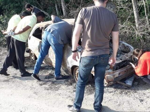 Peritos durante análise do carro onde a ossada estava (Foto: PM Corumbá)