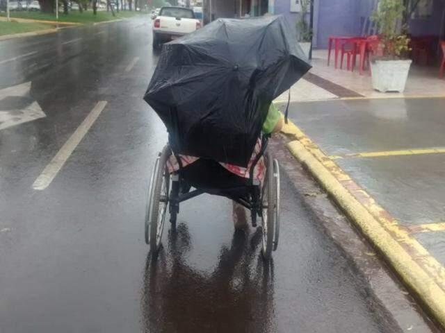 Cadeirante se protegendo com guarda chuva quebrado no Santa Fé (Foto: Simão Nogueira)