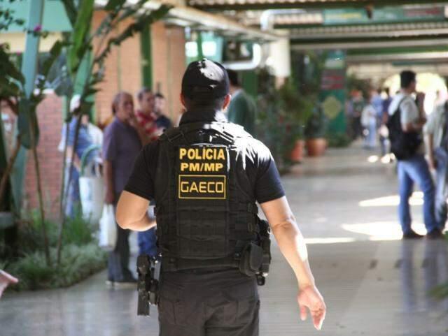 Policial em cumprimento de mandado de prisão, busca e apreensão no Detran (Foto: Marcos Ermínio)