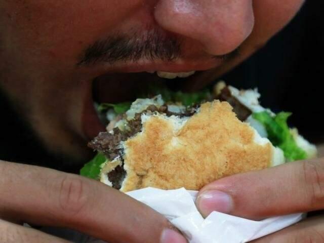 """Homem """"se joga"""" em um sanduíche, em hamburgueria de Campo Grande. Pesquisa de 2017 revelou que quase 70% da população de MS está com sobrepeso. (Foto: Arquivo/Alcides Neto)"""
