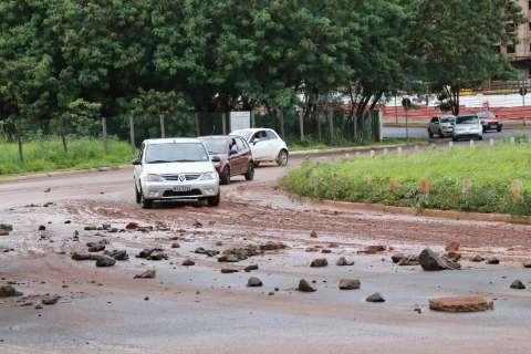Lama e pedras permanecem em rotatória após chuva e enxurrada