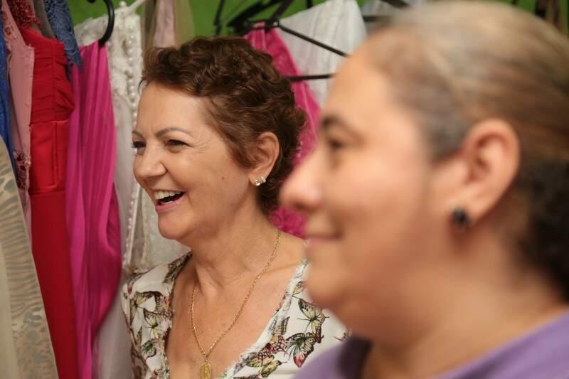 O encanto da mãe ao ver a filha vestida, ao lado de quem está costurando o sonho da noiva, Rosana.